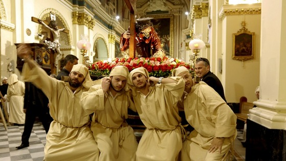 Statue bearers strain as they prepare to lift the statue of Christ the Redeemer at the start of a Good Friday procession in Valletta, Malta
