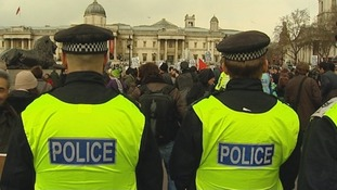 Police officers stand guard as protesters gather at London's Trafalgar Square.