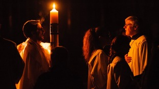 Clergy light the Paschal candle during the Easter vigil mass at Westminster Cathedral