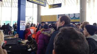 Crowds wait for news following the evacuation of Terminal One at Manchester Airport