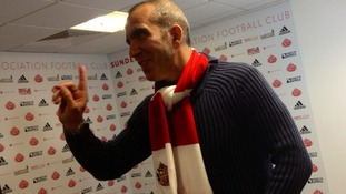 The former Swindon manager Paolo Di Canio tries on a Sunderland scarf for size