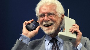 Martin Cooper holds the Motorola DynaTAC phone, the world's first commercial handheld cellular phone and a more recent model.
