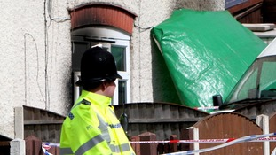 Police guarding the burnt out home of Mick Philpott last year