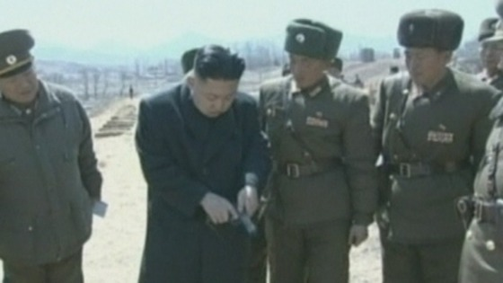 Kim Jong-Un is given a handgun by one of the soldiers