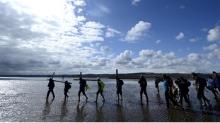 Pilgrims cross a sand bar at low tide to reach the Holy Island of Lindisfarne in Northumberland