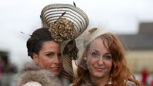 Two women pose in hats for Ladies' Day at the Grand National at Aintree Racecourse