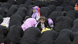 Children sit between women at Friday prayers during a pro-democracy rally