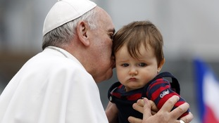 Pope Francis kisses a child during a weekly general audience in Saint Peter's Basilica