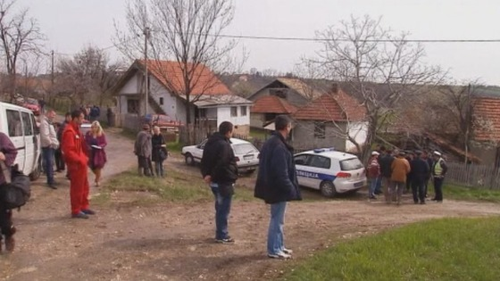 Neighbours and police in the village of Velika Ivanca, thirty miles south east of Belgrade