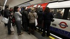 Passengers try to get on board a crowded tube train.
