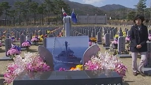 A mother visits her son's grave in a war cemetery in South Korea