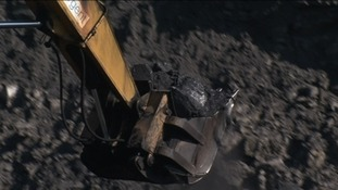 Coal being lifted out of mine by a digger