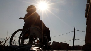 A person sitting in a wheelchair facing the sun.