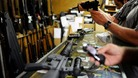 Customers look at rifles for sale at the Bullet Hole gun shop in Sarasota, Florida