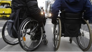 Two people in wheelchairs crossing the road.
