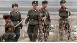 North Korean soldiers seen working with shovels on Hwanggumpyong Island, opposite the Chinese border.