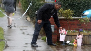 A police officer places flowers at the property  Ruislip, northwest London.