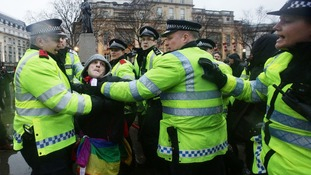 Police talk to a man during a Thatcher's dead 'party', organised via Facebook, in Trafalgar Square.