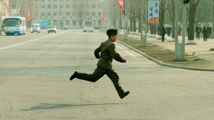 A North Korean soldier runs across a street in Pyongyang yesterday.