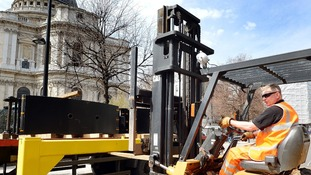 A fork-lift driver unloads steel road barriers that will be used in the ring of security around St. Paul's for Baroness Thatcher's funeral.