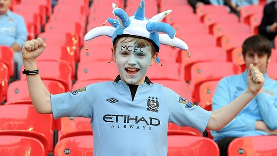 A young Manchester City fan cheers on his team in the stands