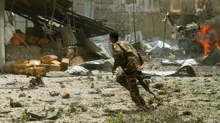 A Somali soldier runs near the scene of a deadly blast in Mogadishu