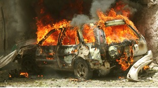 A car goes up in flames near the scene of a blast in Mogadishu