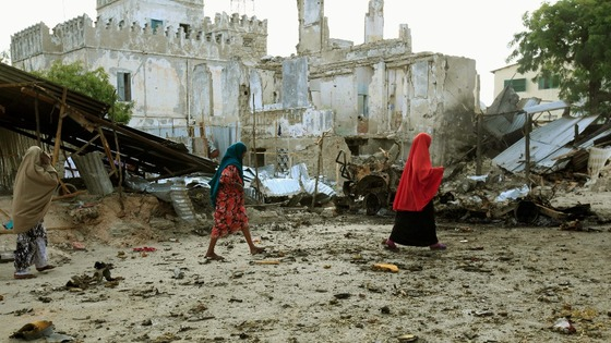 Somali women walk past the site of a deadly blast in Mogadishu