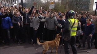 Fans chant as the police keep them back.