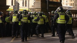 Police in riot gear run to hold barricade after the derby match.