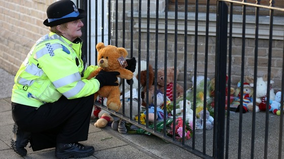 A PCSO lays a tribute from a member of the public outside the flat where the three children were found