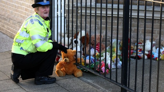 A PCSO lays a tribute from a member of the public outside a flat in Lowestoft