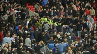 Trouble breaks out in the stands between the Millwall fans and police.