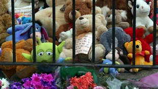 Flowers, bears and other toys have been left outside the house.
