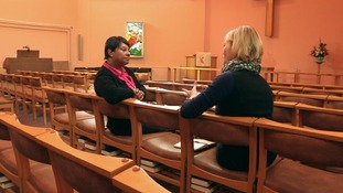 Two ladies sit on chairs in a church chatting
