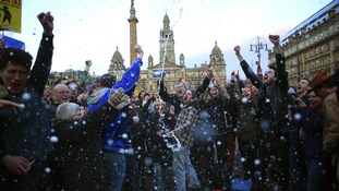 Revellers spray a bottle of champagne on day Baroness Thatcher died at George Square in Glasgow.