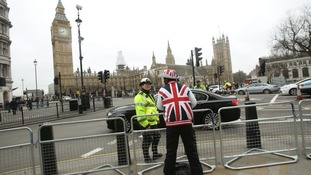 A spectator sporting a Union Flag hat and coat speaks to a police officer at Parliament Square.