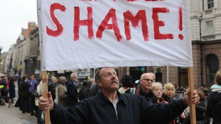 A man holding a 'rest in shame' banner outside the Royal Courts of Justice.