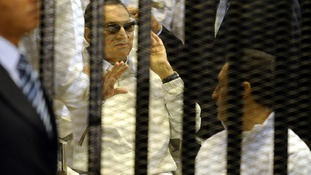 Hosni Mubarak waves as he sits behind bars during a hearing in his retrial last week.