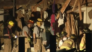 Firefighters pick through the remains of a building in West