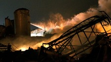 Smoke rises as water is sprayed at the burning remains of the fertilizer plant