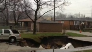 Three cars slid into the sinkhole and a fourth was towed from the edge