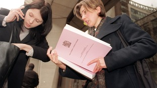 Journalists collect a copy of the Stephen Lawrence Inquiry,