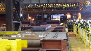 Workers look on as the first piece of steel is produced