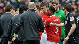 Luis Suarez (L) refuses to shake Patrice Evra's hand at Old Trafford