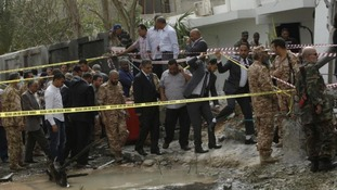 Libyan Interior Minister Ashour Shuail (C) inspects the scene near the French embassy in Tripoli, after it was hit by an apparent car bomb
