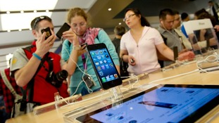 Customers looking at an iPhone5 inside the Apple Store