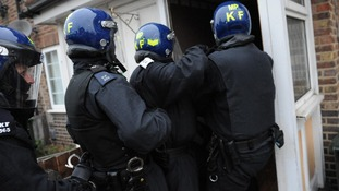 Police officers enter a house as part of a crackdown on gang crime
