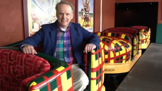 Animator Nick Park sitting in one of the slipper shaped cars on the new ride.