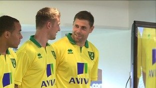 Norwich City captain Grant Holt shows off the club's new home strip with teammates
